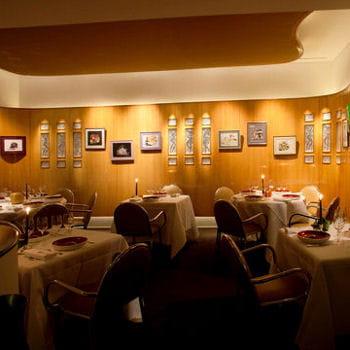 sièges de cuir, portraits au mur et assiettes de lalique, le décor de l'arpège