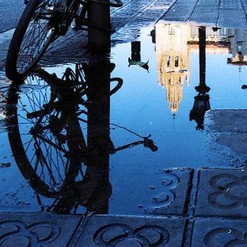 reflet de la ville sur une flaque d'eau dans une rue de barcelone.