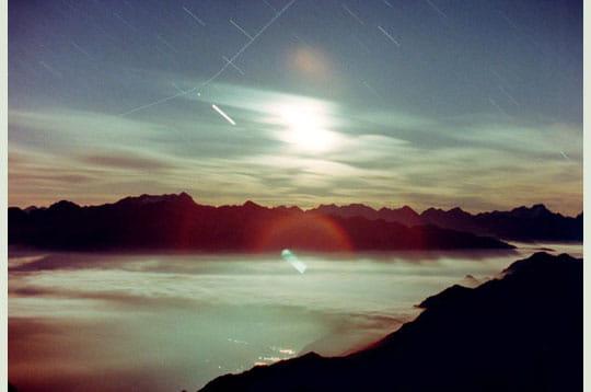 'la lune en croissant projète la silhouette des montagnes sur la mer de nuages.