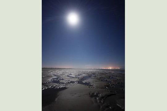 'a marée basse, l'océan a laissé des flaques et lissé le sable. la pleine lune