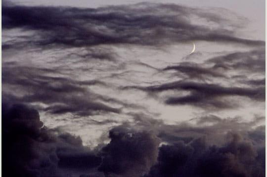 des nuages gris envahissent petit à petit le ciel. un croissant de lune parvient